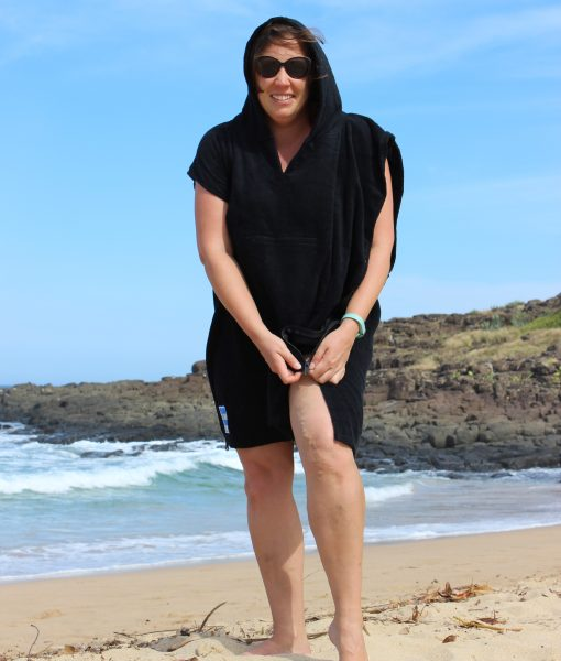 zipping up a black beach towel poncho